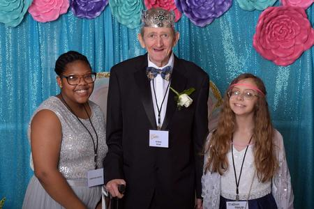 Man with downs syndrome and two volunteers (or buddies) posing at the photo booth; female buddy and prom king are wearing feather boa's and the male buddy is wearing a top hat