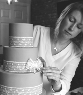 Gemma-Hart-owner-decorating-3-tier-cake-with-ribbon