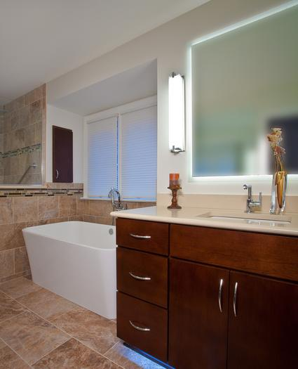 Soaking bathtub with knee wall and wood cabinetry in bathroom after remodel.