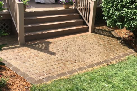 Small paving brick patio off of deck. Decorative circle design laid in the center and water proofed.