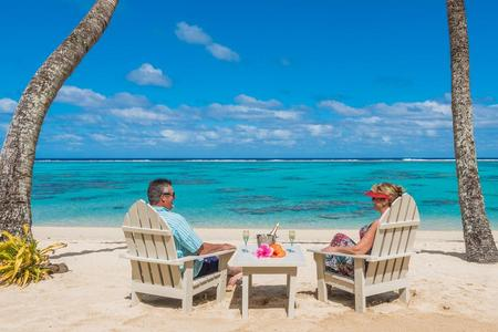 man and women seated on a Rarotongan beach