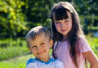2 deaf kids smiling in meadow