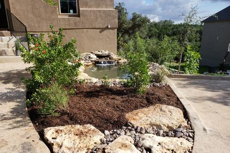 a landscape design in cross mountain ranch with oak trees and two beautiful beds with stone borders