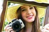 Woman shown in a picture frame smiling, wearing large straw hat holding a camera .