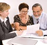 Image of two females and one male reviewing a lease agreement.
