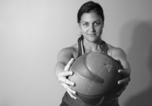 Woman with athletic physique lifting a medicine ball