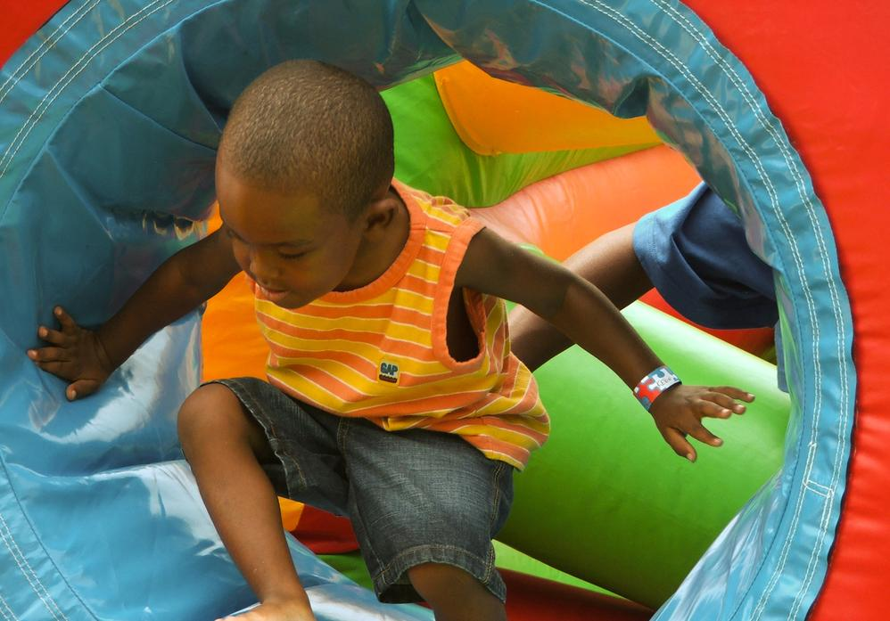 Child playing on an inflatable game at a company picnic.