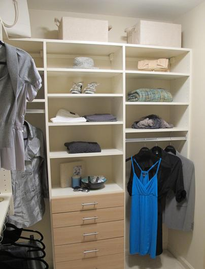 Multi level hanging rods and custom shelving unit in master closet