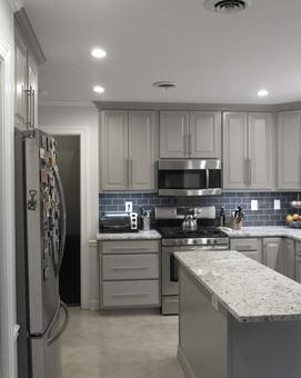 Gray cabinets in kitchen are accented by a dark gray backsplash and a light countertop