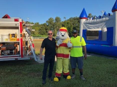 Two men pose with a mascot dog in firefighter's clothing with a firetruck and bouncy house in the background.