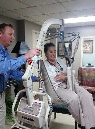 Valerie Smith, RN, practices using the patient lift machine