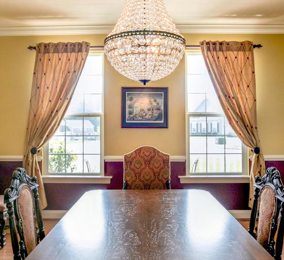 This traditional, Maryland, home mixes old with new as you can see by the antique dining set, under the Pottery Barn chandelier. New silk drapes and gold and maroon paint keep with the traditional feel of this space.