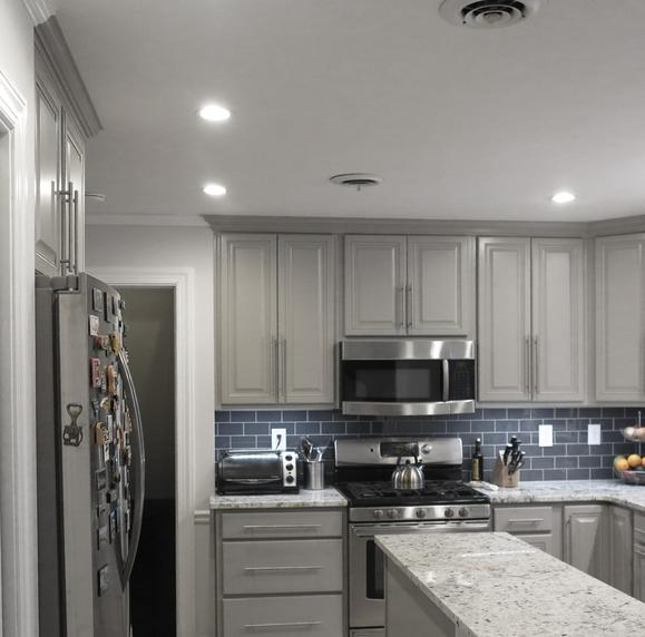 Gray cabinets highlighted by a dark gray backsplash