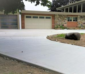 Broom finish concrete driveway with extension, turn around, and parking pad.