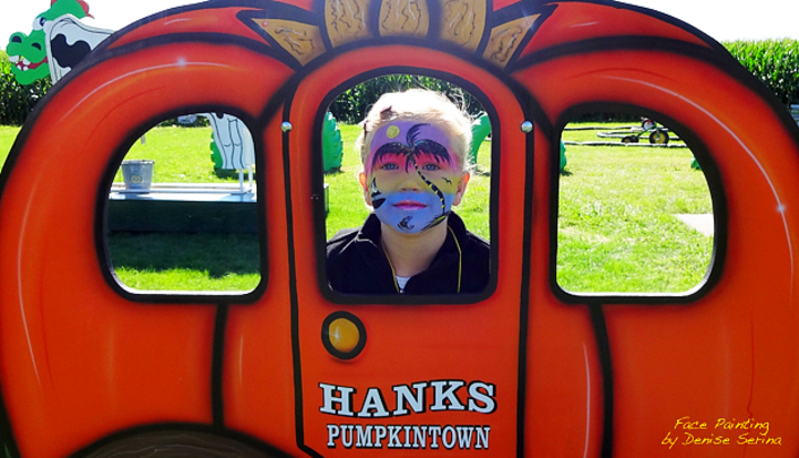 Child with an Island Scene painted on his face standing behind a Pumpkin Carriage Photo Op at Hank's PumpkinTown