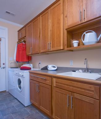 Cherry cabinets, utility sink, tile floors included in laundry room
