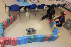 Kindergarters playing on the floor with big blocks.