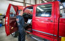 diesel mechanic inspecting interior driver's side of red truck