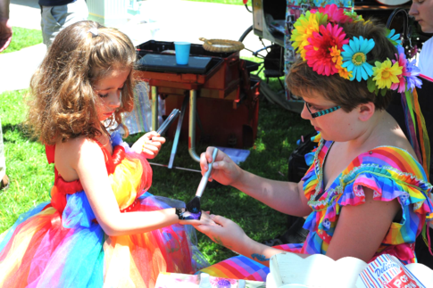 glitter tattoo being applied to a rainbow dressed girl at a rainbow birthday party