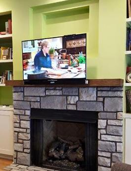 flat screen tv mounted over fireplace with down and out mount pulled down from over the fireplace, charlotte nc flat panel television installation company