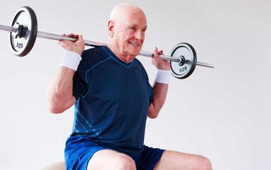 Mature man exercising with a bar on his shoulders for Body conditioning
