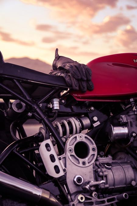motorcycle gloves over cafe racer motorcycle sunset