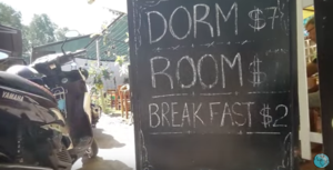 chalkboard on street advertising a hostel with prices, dorm $7 breakfast $2