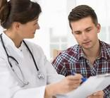 Image of female Doctor and young male patient reviewing test results.