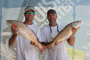 kyle mitternight holding redfish next to Paul smith holding redfish for lousianna saltwater fishing series