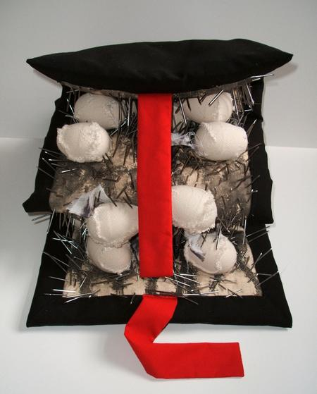 'Graveyard' sculpture by Heejung Kim. Image shows black fabric enclosure with a red tie; inside are nails and fabric covered shapes.