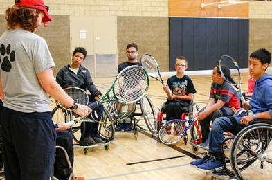 5 people in wheelchairs holding tennis rackets, receiving instruction from one person who is standing and holding a tennis racket.