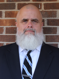 Wes Rollins of All Access Investigation is a middle aged man with a suit and tie, bald head and white beard.