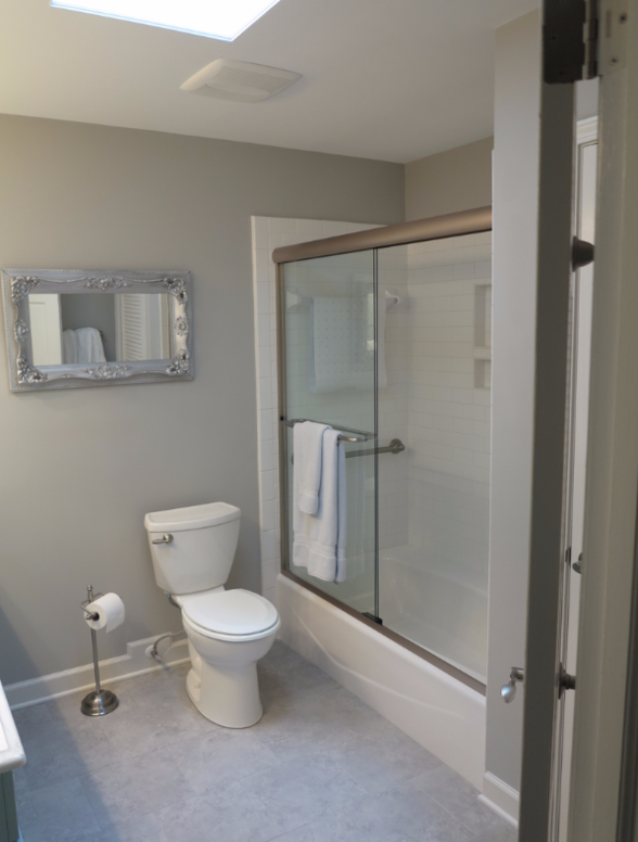 Framed shower enclosure in guest bathroom after remodel