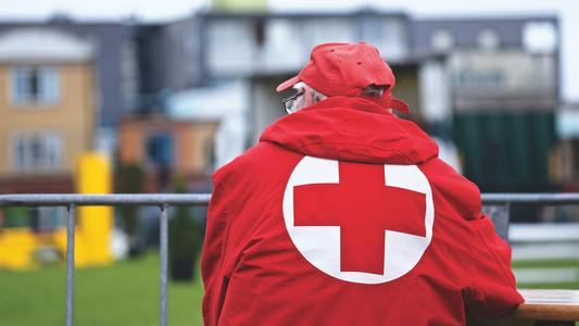 older man wearing red jacket with red and white red cross logo