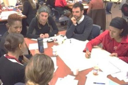 Adults sitting at a table at the Dryades Y to network and discuss what we could all do collectively and individually, as organizations to get our children outdoors to PLAY, LEARN, SERVE AND WORK in communities around the city.