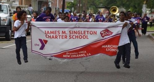 Picture of two students Holding the James m. Singleton banner in front of the Marching Band. The two boys jumped at the same time so they appear to be floating over the road.