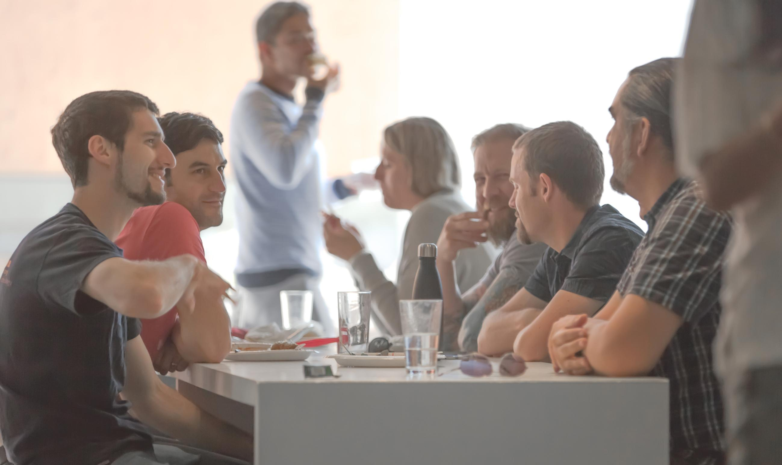 group of males having interaction with blurry office barbecue background