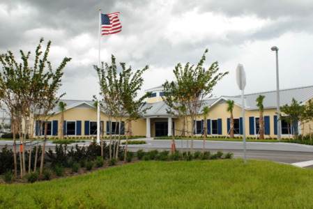 Yellow Airport Authority Building With American Flag and Trees