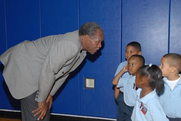 Actor Danny Glover Bent over talking to small children at the Dryades YMCA
