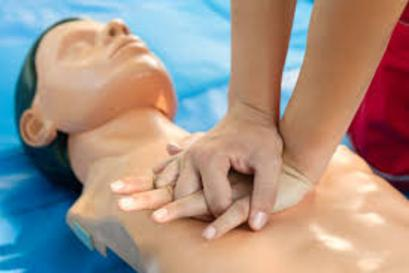 hands on a CPR mannequin doing chest compressions