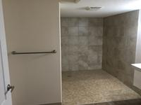 This Bathroom development was completed using commercial 'barrier free' design principles for a customer in a wheel chair. Features include a large custom shower with wheel chair ramp, enlarged man door, grab bars in shower and around toilet, and lowered sink and electrical outlets and switches.