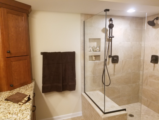 Tiled bench seat in the shower is accented by plumbing fixtures that integrate beautifully with the matching grab bars in this shower.