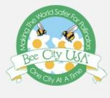 "A circular Bee City USA logo with flowers and bees on it, saying ""Making The World Safer For Pollinators, One City At A Time."""