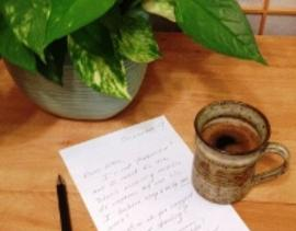 coffee cup with letter and plant, contact ellie hadsall
