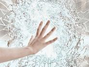 Woman's hand touching a bright clear glass wall that is shattered.