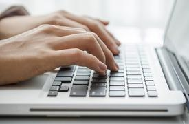 Woman's hands close up shown typing on a laptop keyboard.