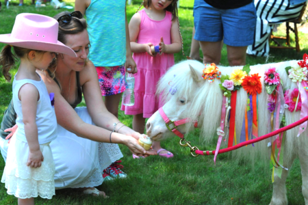 little pink cowgirl feeding Easter Lily mini horse a cupcake at her Peppermint Pony birthday
