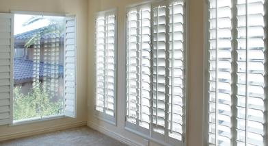 white interior shutters letting some sunshine into the living room