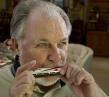Harland Crain plays the harmonica