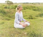 Blonde woman with pony tail sitting crossed legged in a grassy field meditating.